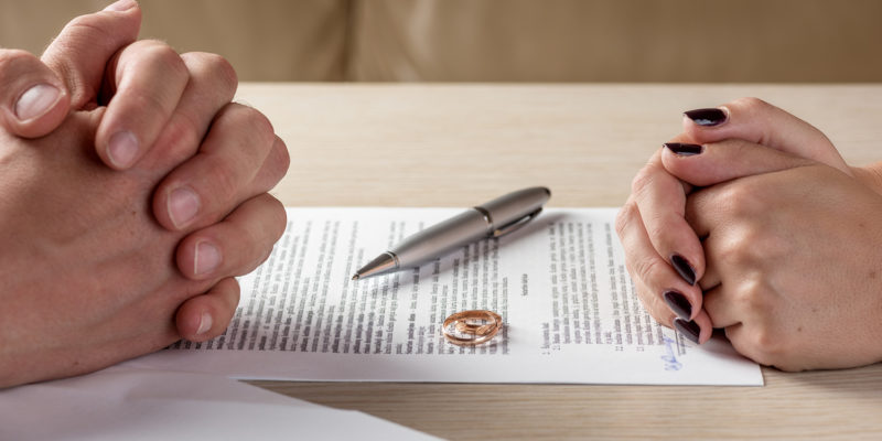 Hands of wife and husband signing divorce documents or premarital agreement