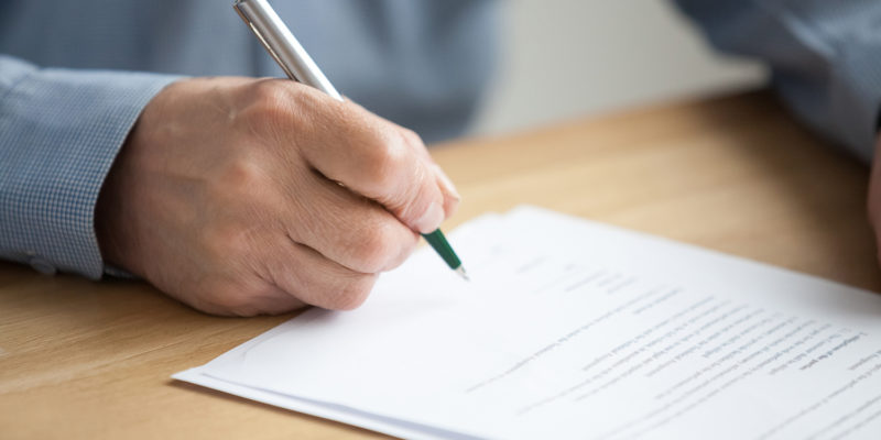 Older male hand signing business document, senior man putting signature on legal paper making investment, elderly aged businessman taking bank loan or insurance, writing will testament, close up view
